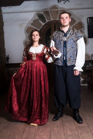 seducer: Young beautiful couple woman and man dance in medieval clothes in room Stock Photo