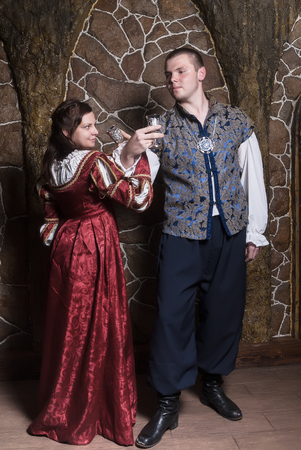 the tempter: Beautiful couple woman and man in medieval clothes in the room Stock Photo