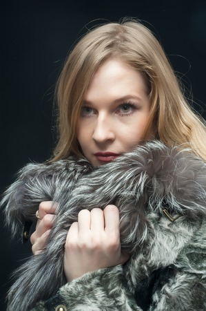 elegance fashion girls look sensuality young: Attractive woman in fur coat over black background
