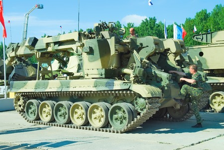 clearer: Nizhniy Tagil, Russia - July 12. 2008: Visitors explore military equipment on exhibition range. Crew of ?ombat engineering vehicle IMR-2MA prepares to motion Editorial