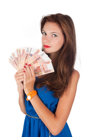 exaggerated: Young girl with freckles cools herself with a fan of money Stock Photo