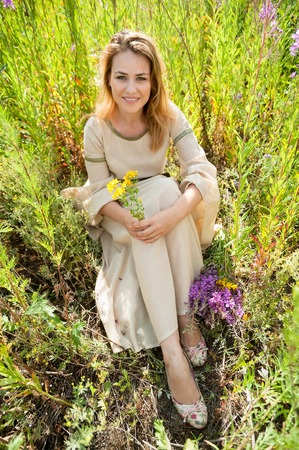 depressed: Attractive woman in traditional dress longs with flowers on fireweed meadow