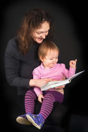 Attractive mother shows pictures in book to her cute little 15 monthes old daughter over black background