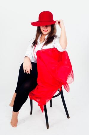 pies bailando: Hermosa bailarina morena con el pelo rojo que descansa en silla sobre fondo blanco