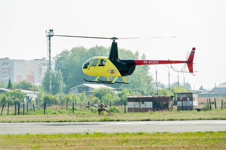 heliport: Tyumen, Russia - August 11, 2012: On a visit at UTair airshow in heliport Plehanovo. Piloting of Robinson R44 Raven shows flying opportunities Editorial