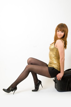 suit case: Young attractive girl sits on suit case over white background