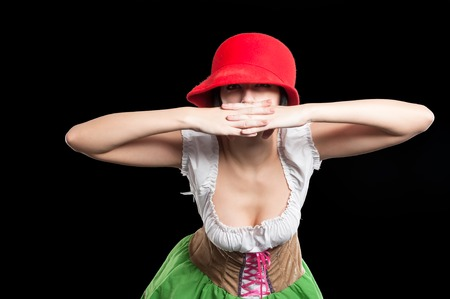 feminity: Beautiful woman in german costume with red hat. Isolated on black