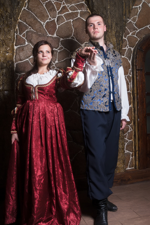 tempter: Beautiful couple woman and man in medieval clothes in the room Stock Photo