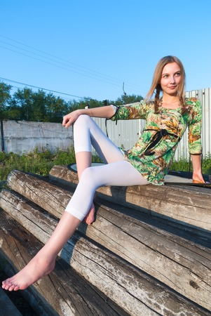 Young attractive woman sits on old railway wooden cross ties photo
