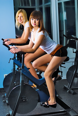simulators: Young beautiful women doing exercise on bicycle simulators in fitness center Stock Photo