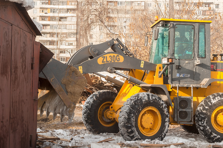 dismantling: Tyumen, Russia - February 16, 2008: Bulldozer works on demolition of old derelict buildings between Profsoyuznaya and Severnaya streets Editorial
