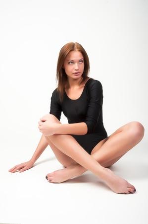 Junge attraktive Frau im Turner-Anzug auf dem Boden auf weißem Hintergrund