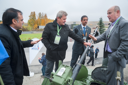 Delegation: Nizhniy Tagil, Russia - September 27. 2013: Russia Arms Expo-2013 exhibition. Representatives of JSC Military-industrial Company communicate with foreign delegation members on tank