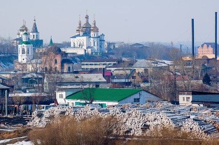 saints peter and paul: Big pile of logs ready for production on plywood factory on foreground. Voznesensko-Georgiyevsky church in middle. Holy Trinity Monastery. Church of Saints Peter and Paul and Holy Trinity Cathedral on background. Tyumen. Russia