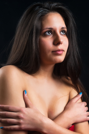 sexy topless woman: portrait of lovely naked woman covering her breast against black background