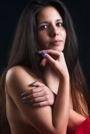 junge nackte m�dchen: Portr�t der sch�nen nackten Frau, die ihre Brust vor schwarzem Hintergrund bedeckt