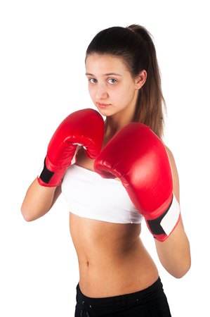 Pretty young woman wearing boxing gloves posing in combat stance looking at camera. Fit young female boxer ready for fight on whitebackground Stock Photo