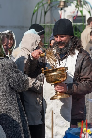 believers: Tyumen, Russia - April 27, 2008: The orthodox priest consecrates believers and Easter cakes with the help an aspergillum. Easter