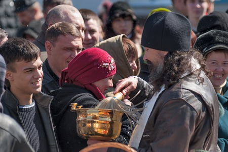 beautiful hands: Tyumen, Russia - April 27, 2008: The orthodox priest consecrates believers and Easter cakes with the help an aspergillum. Easter