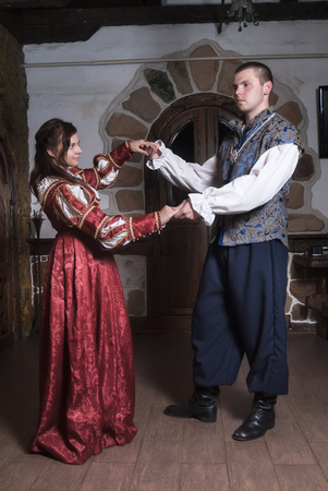 the tempter: Young beautiful couple woman and man dance in medieval clothes in room Stock Photo