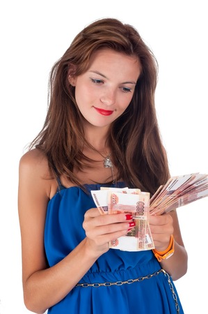 exaggerated: Attractive smiling girl with freckles cools herself with a fan of money