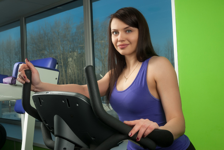 stationary bike: Athletic girl pedaling on a stationary bike at the gym