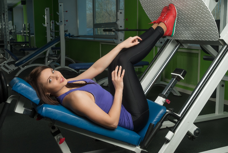 simulator: Young brunette building leg muscles in simulator at the gym