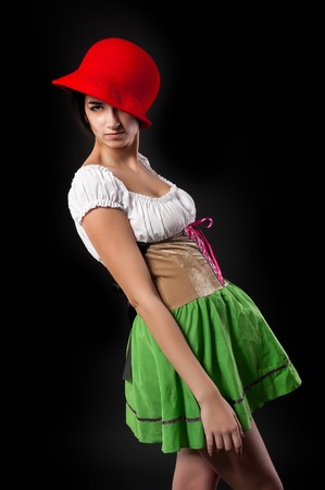 nude adult: Beautiful cool woman in german beer girl costume with red hat. Isolated on black