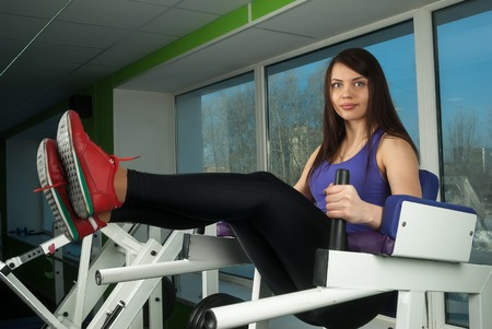 sexy young girl: Young woman working her quads at machine press in the gym. Pretty Hispanic brunette exercising in a simulator in a gym