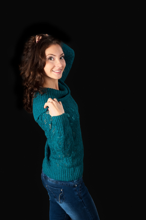 nude girl young: Sweet young girl, with curly hair in sweater over black background, waist up