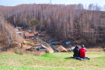 autumn young: Young couple sit on hill over old rural part of Tobolsk. Russia Stock Photo