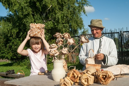 birchen: Suzdal, Russia - August 29, 2009: The elderly master in production of birch bark products with the granddaughter shows goods in the museum of wooden architecture
