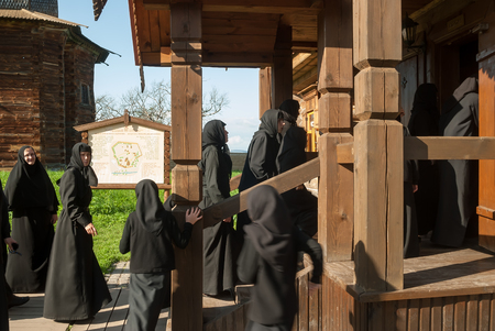museum visit: Suzdal, Russia - August 29, 2009: Novices of convent visit museum of wooden architecture