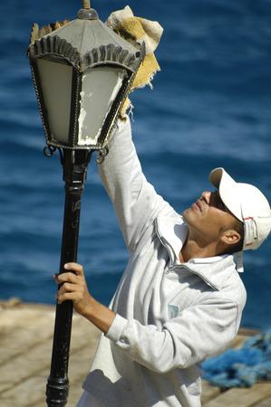 light duty: Hurghada, Egypt - November 7, 2006: Sunrise holidays resort hotel. Employee of hotel dusts a lamp