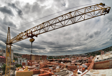 grey  sky: Construction crane against the grey sky and city houses