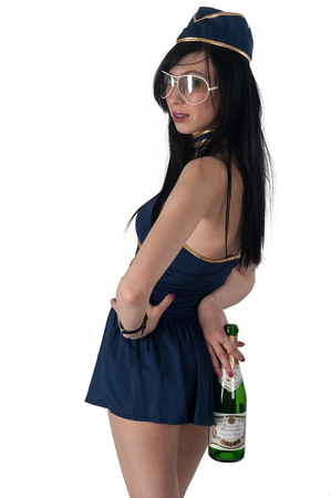 Attractive young stewardess with wine bottle over white background photo