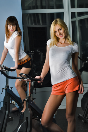 simulators: Young women exsercising on bicycle simulators in fitness center