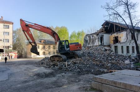 demolishing: Tyumen, Russia - April 29, 2016: Excavator demolishing barracks for new construction project. Kievskaya street 70