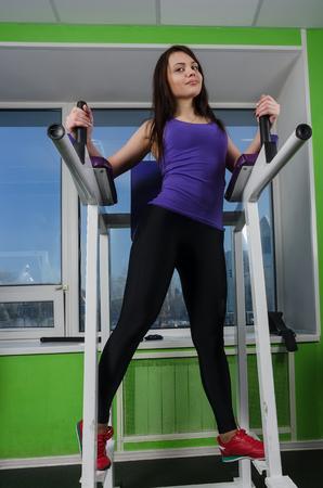 simulator: Beautiful girl in sports club relaxes near simulator