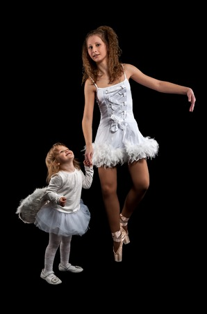 gym dress: Little ballerina dancing with ballet teacher in dance studio. They both wearing a white tutu and leotard Stock Photo