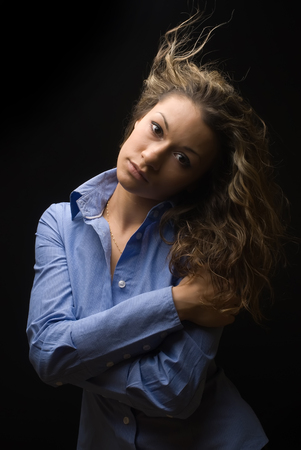 Beautiful caucasian young woman in blue shirt with brown curly hair over black background photo