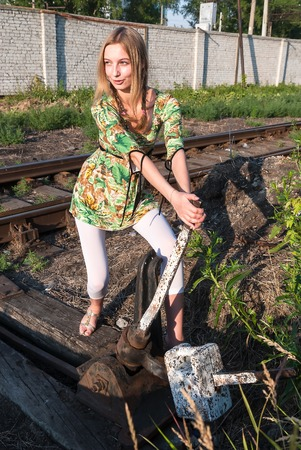 Attractive young woman throws old style railway switch photo
