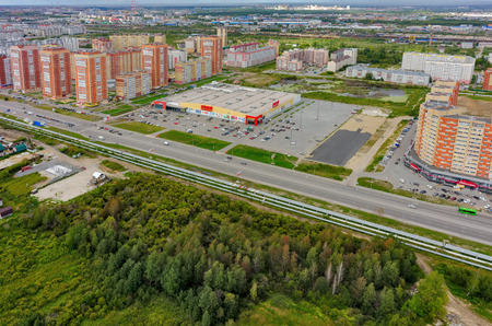 okey: Tyumen, Russia - August 7, 2015: Okey shopping mall of household goods with a lot of parking space, East-2 residential district. Aerial view