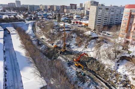 residential tree service: Tyumen, Russia - February 15, 2016: Aerial view onto construction works on strengthening of Tyumenka river bank near Polevaya Street