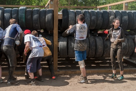 sportsmen: Tyumen, Russia - June 11, 2016: Race of Heroes project on the ground of the highest military and engineering school. Sportsmen move between old tires. Human birth stage Editorial