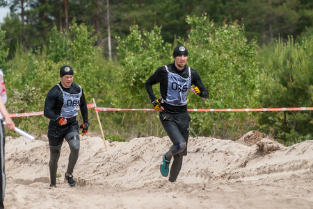 sportsmen: Tyumen, Russia - June 11, 2016: Race of Heroes project on the ground of the highest military and engineering school. Sportsmen run between stages