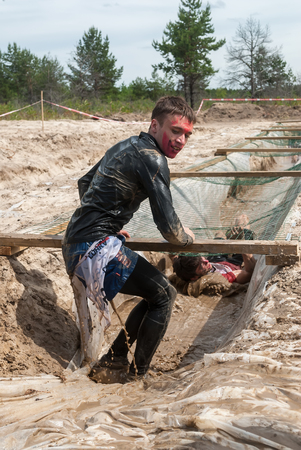 creep: Tyumen, Russia - June 11, 2016: Race of Heroes project on the ground of the highest military and engineering school. Guardroom stage. Men creep on an entrenchment with sand and water under net