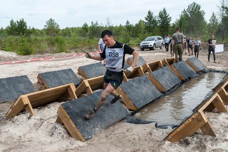 Tyumen, Rusia - 11 de junio, 2016: Carrera de los Héroes del proyecto sobre el terreno de la más alta escuela militar y la ingeniería. Los participantes llevan a cabo ejercicios anti-gravitación