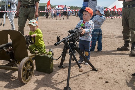 considers: Tyumen, Russia - June 11, 2016: Race of Heroes project on the ground of the highest military and engineering school. Exhibition of weapon. The boy considers an easel machine gun