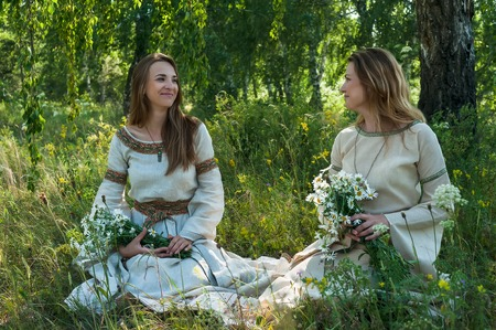 Attractive women in traditional russian clothes relaxing at nature background. Ivan Kupala Holiday Celebration Stock Photo